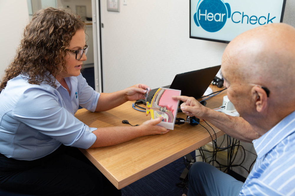 audiologist explaining hearing loss with ear model
