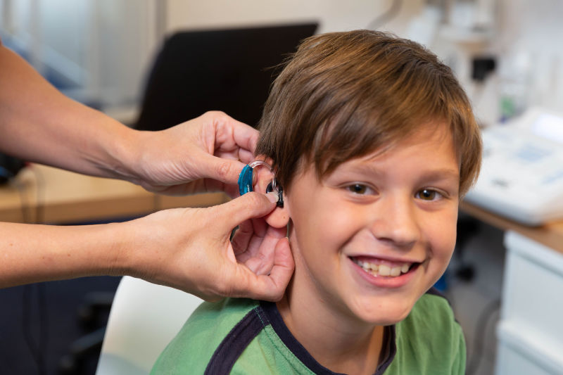 boy happy to have his new hearing aid