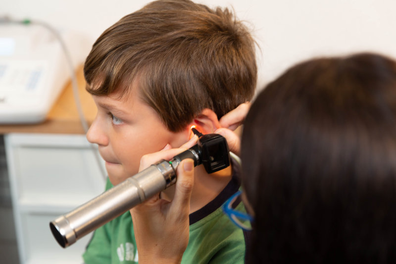 boy with audiologist inspecting ear