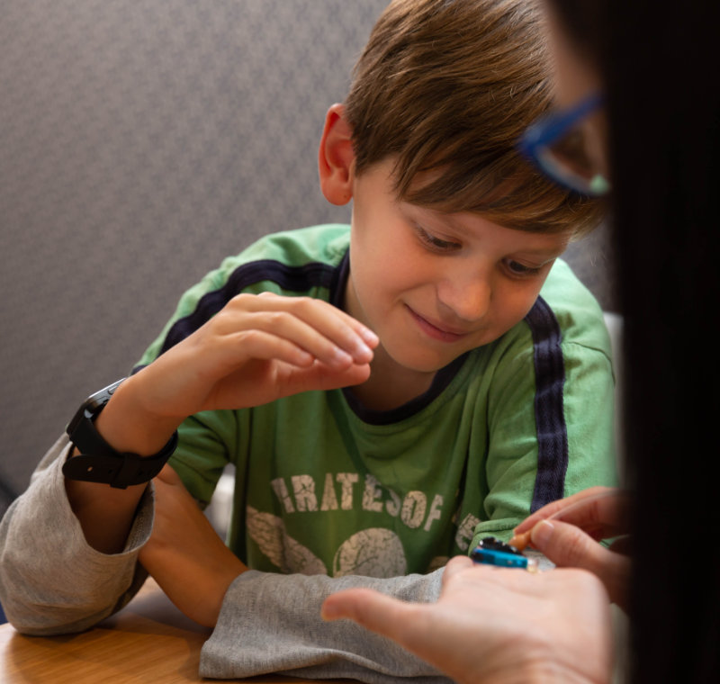 boy with audiologist looking at hearing aid