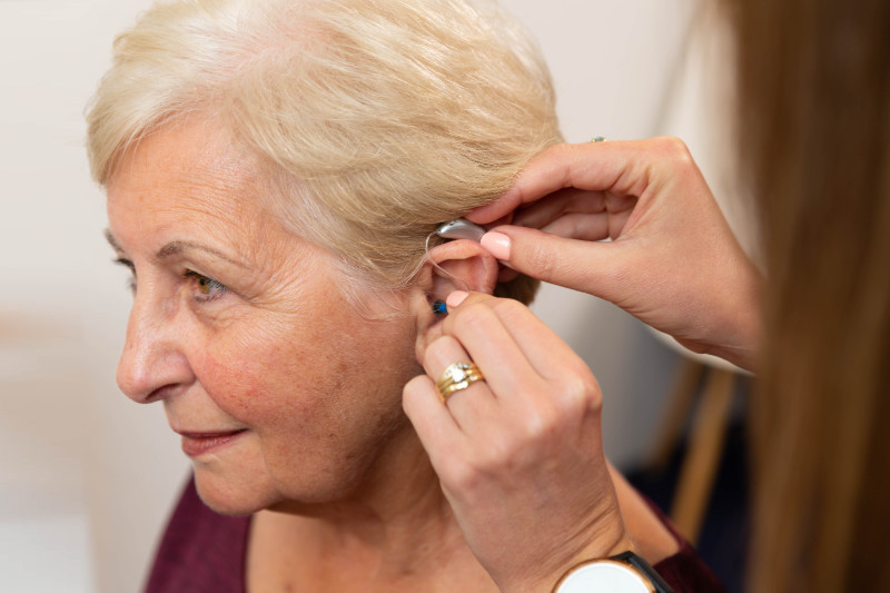 hearing aid being fitted into womans ear