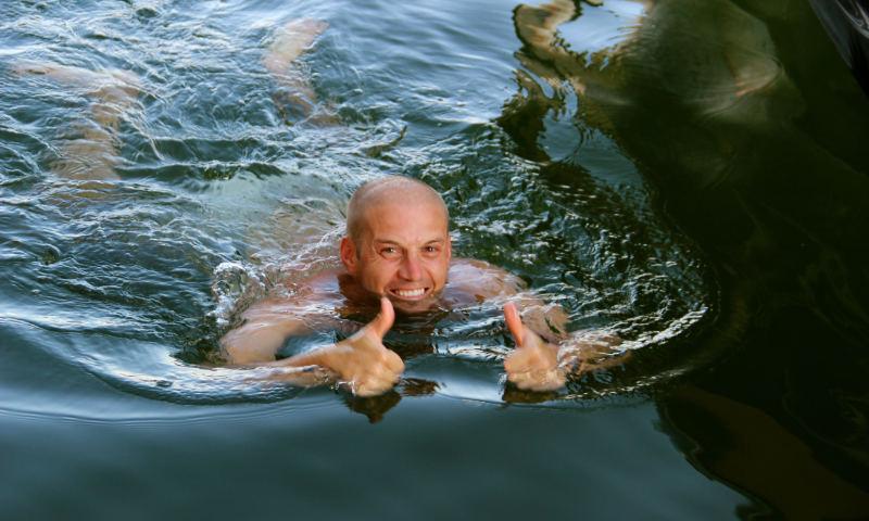man swimming ear plugs