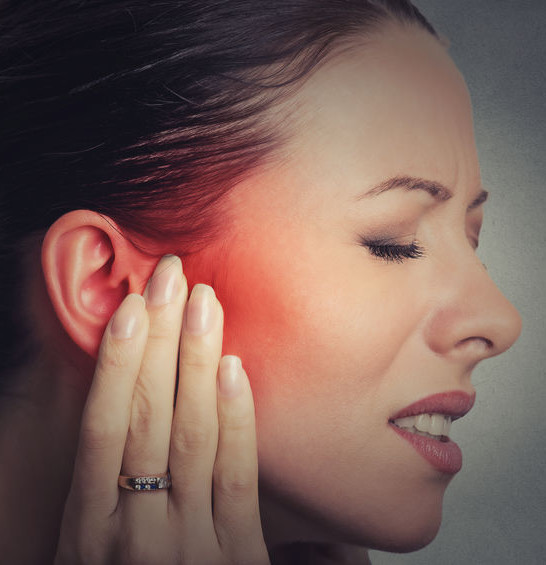 woman has hand on ear ringing tinnitus